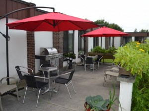 Outdoor dinig and seating area at the back of building, with raised flower beds and red umbrellas