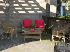 Outdoor seating area with love seat and red cushions under trellis