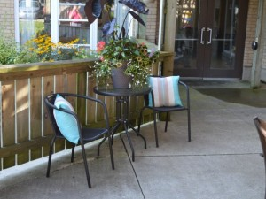 Outdoor seatin area at front entrance of building with colourful pillows and flowers on small table