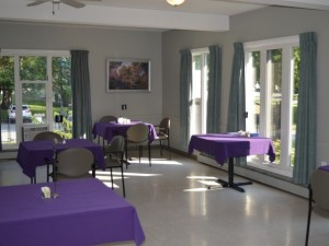 Indoor seating area with three large windows, and tables with purple table cloths