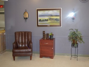 Indoor seating area with large brown leather chair, and a landscape painting hung on the wall