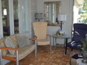 Seating area in a sunroom with love seat and two chairs