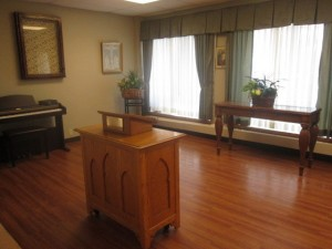 Indoor chapel area with two large windows and piano