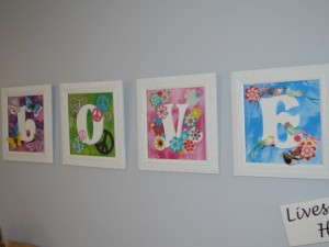 four single framed paintings hung to spell the word love.