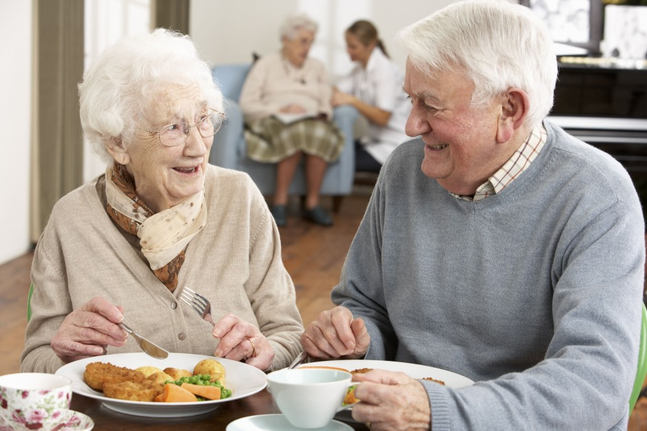 Elderly man and woman conversing and eating food