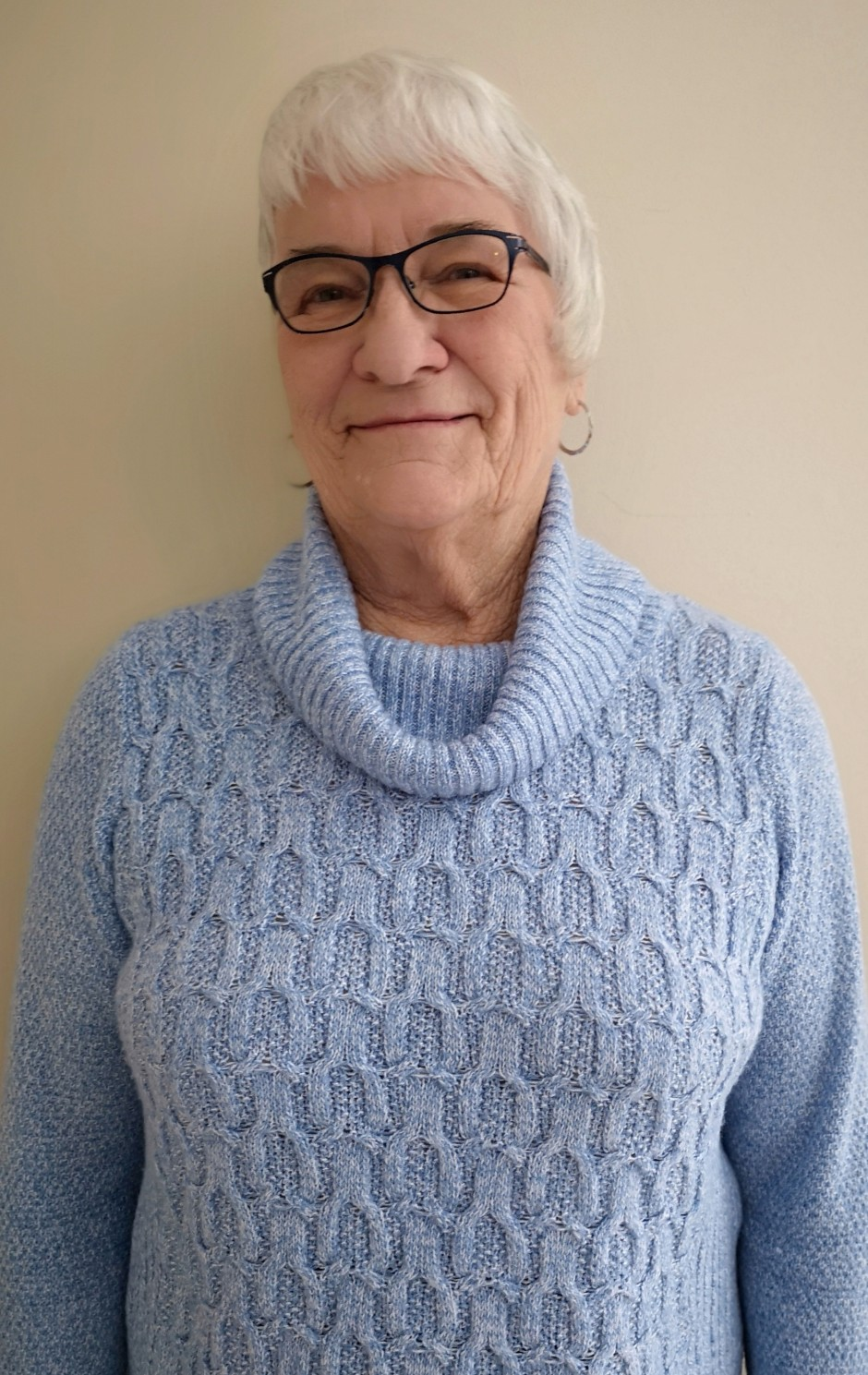 Elderly woman in light blue knit sweater wearing glasses, smiling