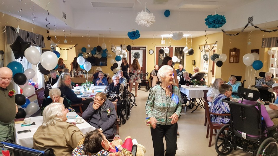 A party room full of elderly men and woman chatting and smiling