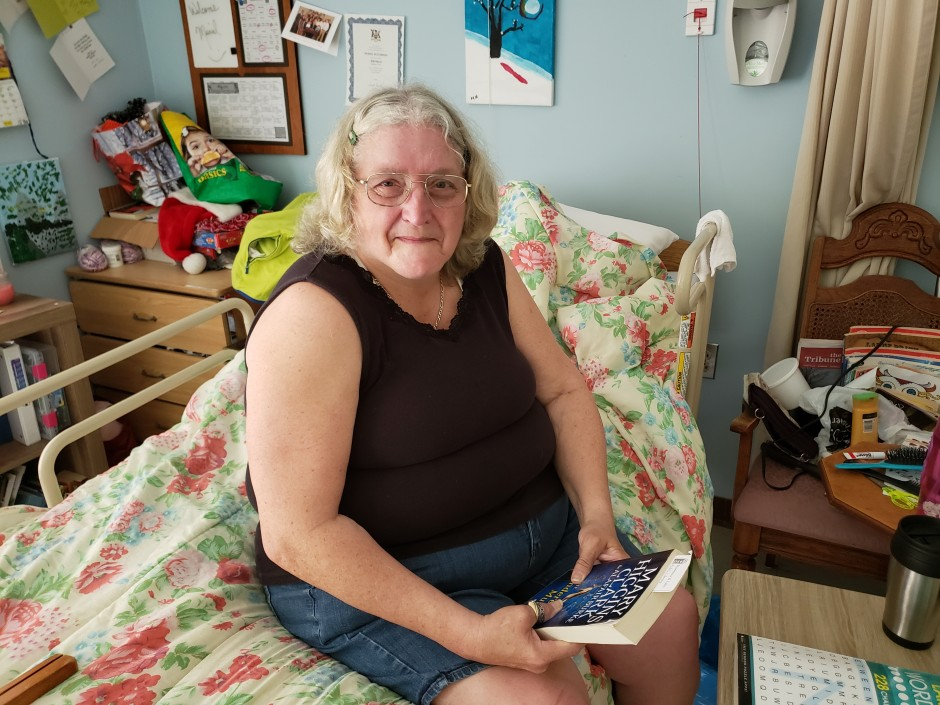 elderly woman sitting in on single bed suite holding a book