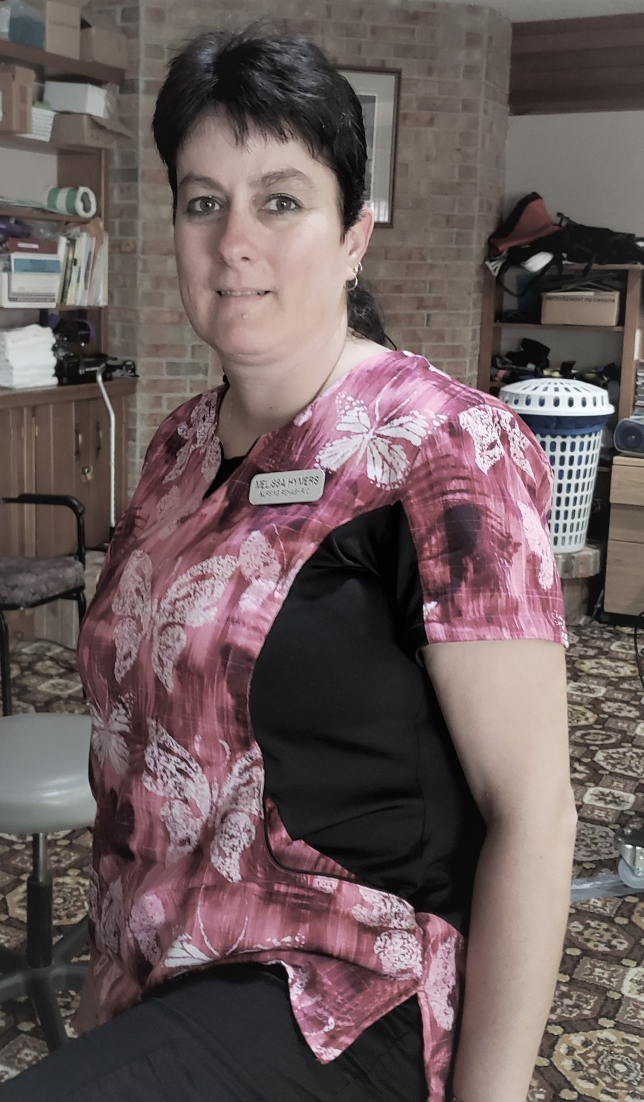 Portrait of personal support worker in pink butterfly print uniform