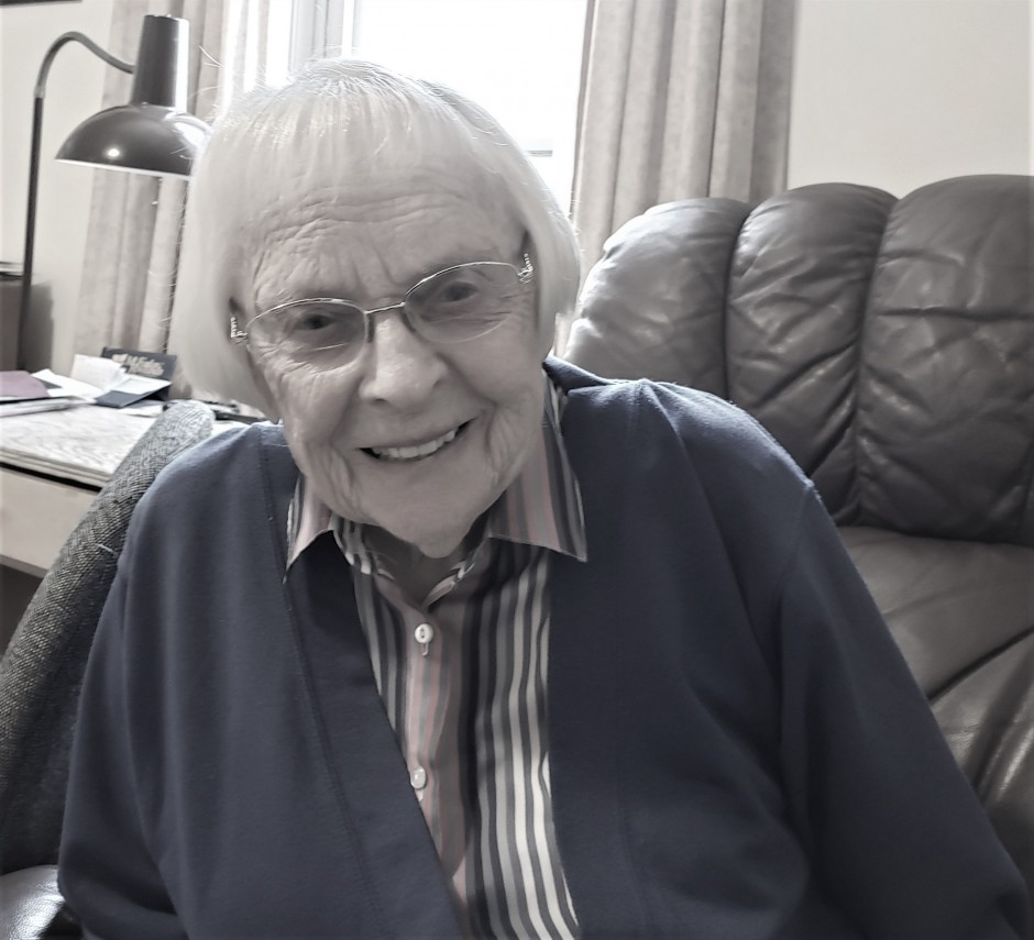 Elderly woman wearing blue cardigan and glasses smiling