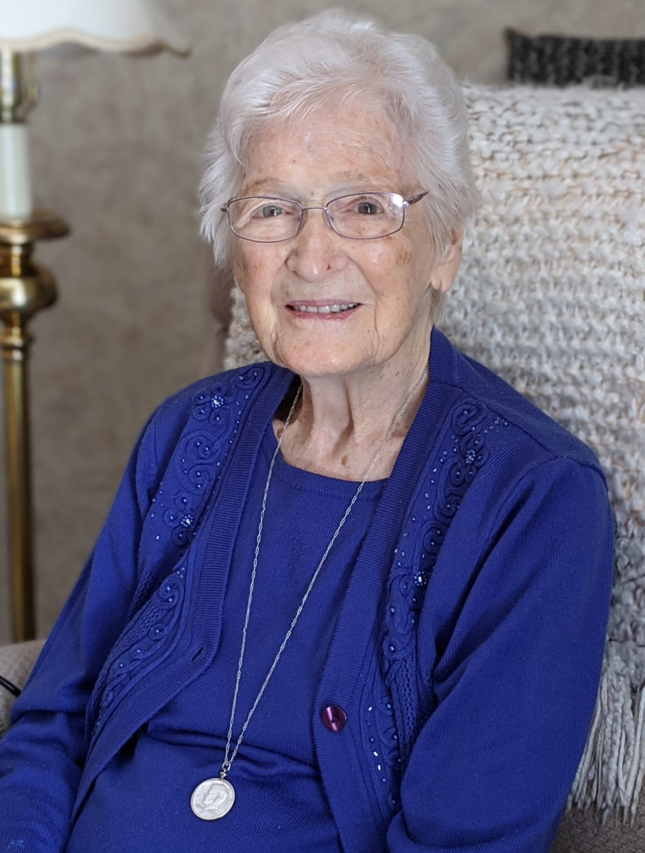 Elderly woman wearing a cobalt blue top and glasses smiling