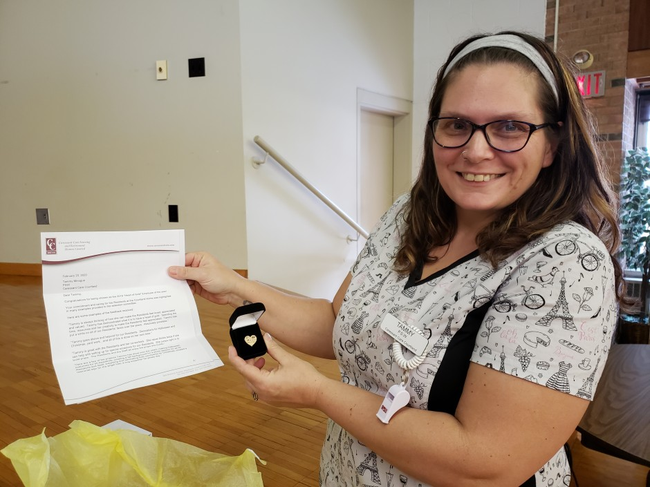 Image of Tammy smiling holding a letter and pin